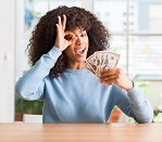 African american woman holding dollar bank notes with happy face smiling doing ok sign with hand on eye looking through fingers